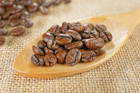 closeup scoop of coffee beans on jute background photo