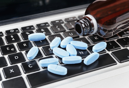 unlawful: close-up pills on computer keyboard, concept online selling medicine Stock Photo