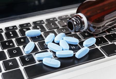 Primer plano píldoras en el teclado del ordenador, concepto en línea la venta de la medicina Foto de archivo