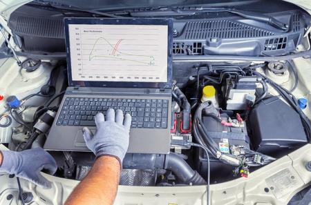 mecanico automotriz: Mec�nico de autom�viles profesional que trabaja en el servicio inform�tico de reparaci�n de autom�viles Foto de archivo