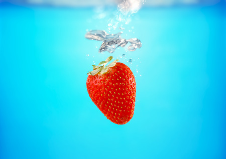 Fresh strawberry dropped splashing in blue water