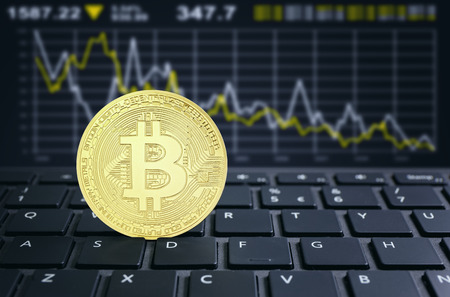 Bitcoins on a laptop keyboard virtual cryptocurrency concept Stok Fotoğraf