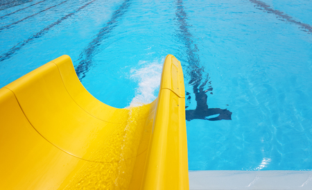 Detail of yellow slide chute in the pool