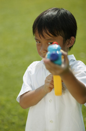Young boy  playing with water gun Stock Photo