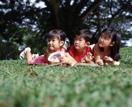 Three children lying on grass reading a book