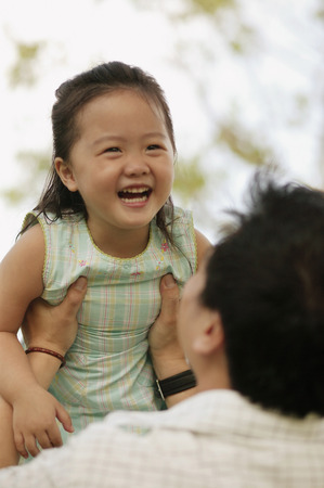 Father lifting young daughter.