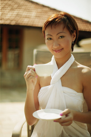 look pleased: Young woman holding cup and saucer, looking at camera