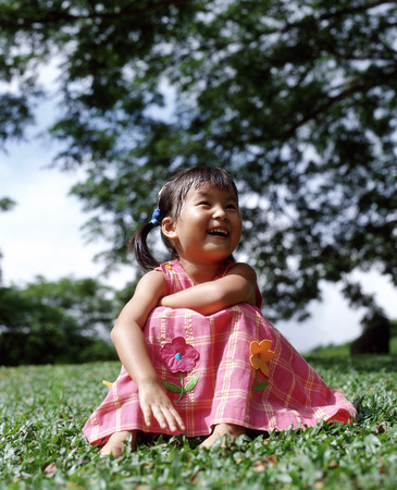 Girl sitting on grass laughing, tree in background