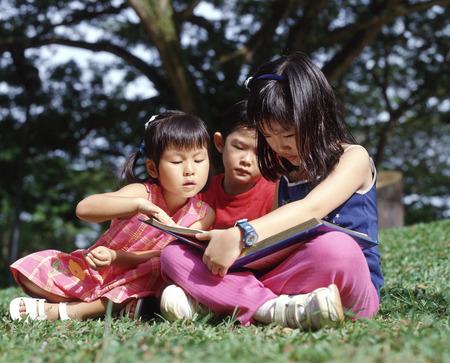 Three children sitting on grass reading a book