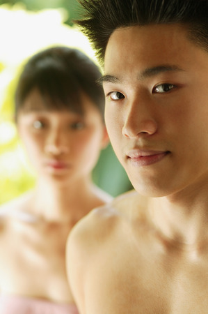 Young man looking at camera, woman in the foreground