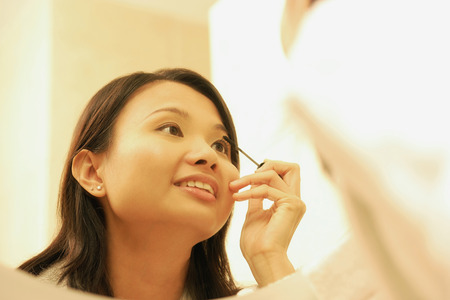 Woman putting on mascara. Stock Photo