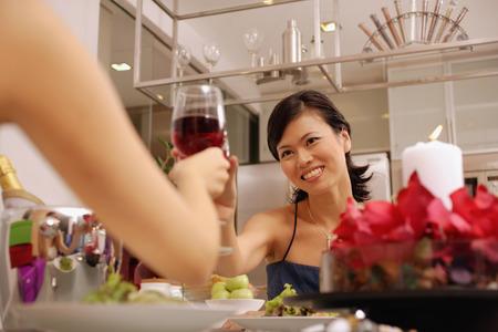 Women raising wine glass, toasting Stock Photo