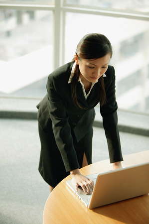 Young woman standing, using laptop Imagens