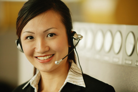handsfree device: Young woman wearing hands-free device, looking at camera