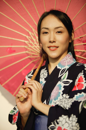 Young woman in kimono, holding an umbrella