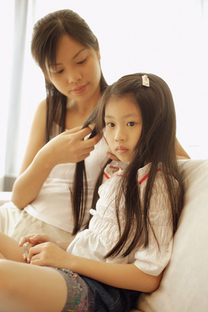 braiding: Mother and daughter, sitting side by side, mother braiding daughters hair.