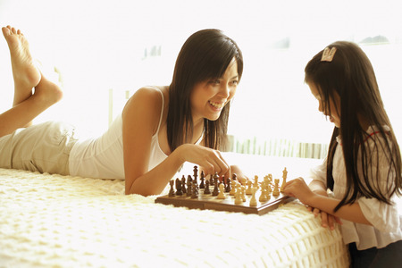 6 7 years: Mother and daughter playing chess in bedroom LANG_EVOIMAGES
