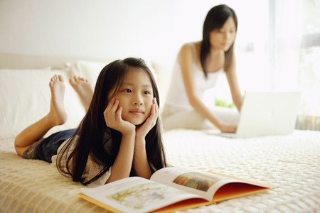 Mother and daughter in bedroom, mother using laptop, daughter lying down with book open in front of her