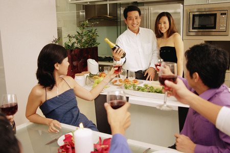 Group of friends having a dinner party at home, some raising wine glass