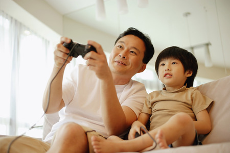 3 4 years: Father and son sitting on sofa, playing with video game, low angle view