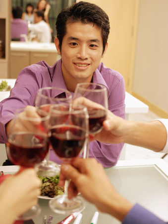 toasting wine: Friends toasting wine glasses across dinner table, over the shoulder view