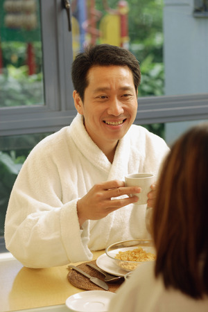 facing each other: Couple facing each other, holding cups of coffee, man smiling