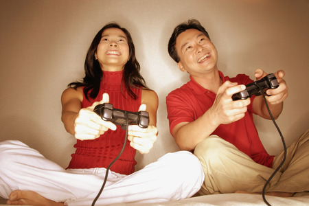 Man and woman playing with handheld video game, looking forward