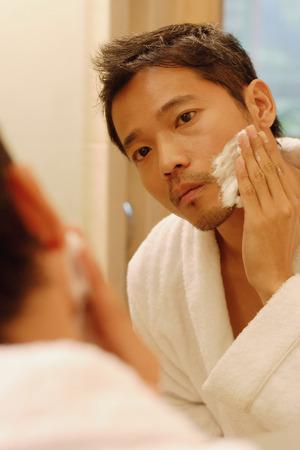 shaving cream: Young man applying shaving cream, looking in mirror