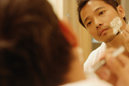 metrosexual: Young man shaving, looking in mirror, over the shoulder view