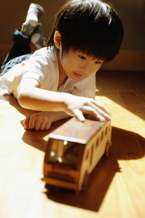 3 4 years: Young boy playing with toy bus, lying on front LANG_EVOIMAGES