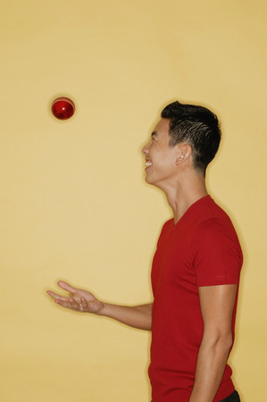 side view: Young man juggling a ball, side view LANG_EVOIMAGES