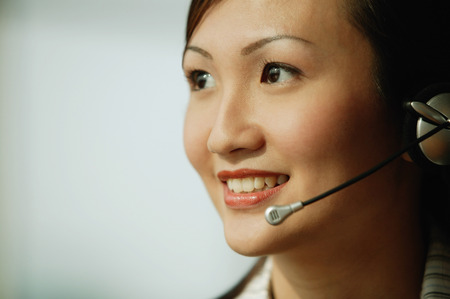 handsfree device: Young woman wearing hands-free device, smiling