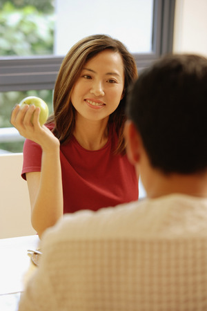 facing each other: Couple facing each other, woman holding an apple
