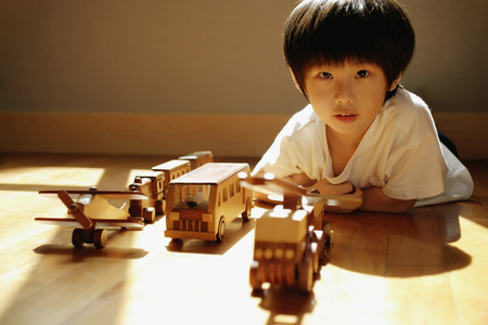3 4 years: Young boy looking at camera, toys in a row in front of him LANG_EVOIMAGES
