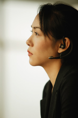 handsfree device: Young woman sitting at desk, using hands-free device LANG_EVOIMAGES