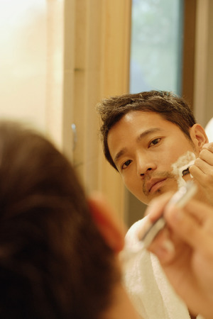 Young man shaving, looking in mirror