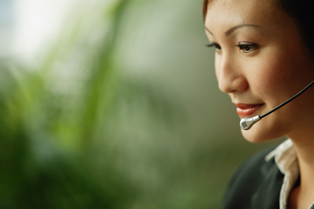handsfree device: Young woman wearing hands-free device, looking down