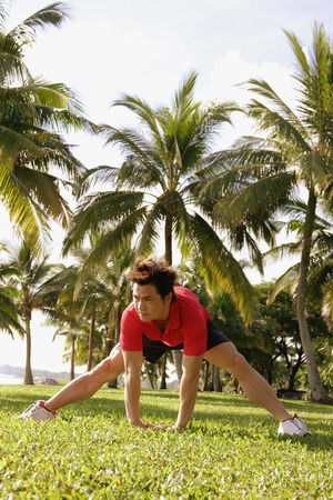 southeast asian ethnicity: Man doing stretching exercises in park, bending forward