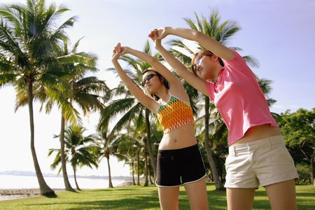 Women doing stretching exercises in park, bending sideways Stock Photo