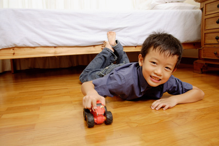 southeast asian ethnicity: Young boy lying on floor with toy car, looking at camera