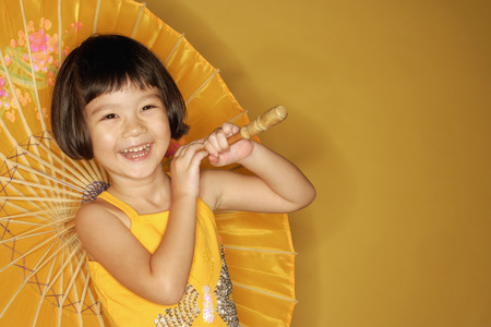 3 4 years: Young girl standing against yellow background, holding umbrella, laughing