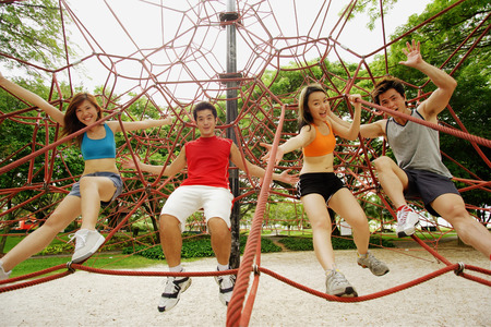 southeast asian ethnicity: Two women and two men, holding on to rope on jungle gym, looking at camera LANG_EVOIMAGES