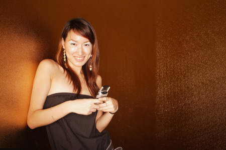 southeast asian ethnicity: Young woman holding mobile phone, looking at camera