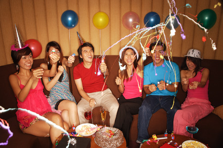 Young adults celebrating with crackers, party hats and balloons