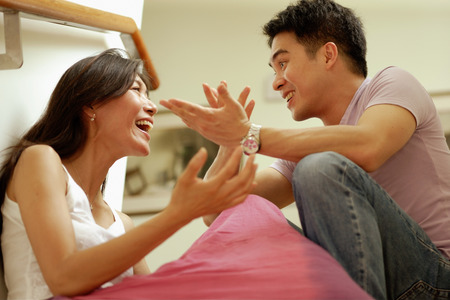 Couple facing each other, hands raised