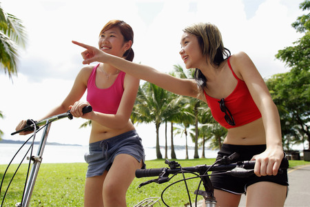 Two women on bicycles, one woman pointing