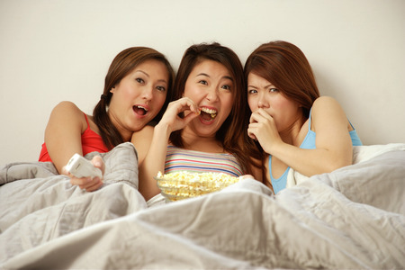 southeast asian ethnicity: Young women lying on bed side by side, eating popcorn