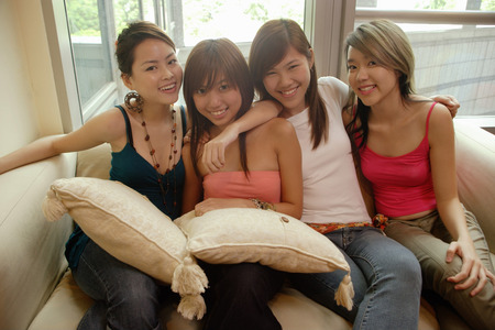 southeast asian ethnicity: Young women sitting on sofa, side by side, looking at camera