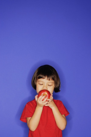 3 4 years: Young girl standing against blue background, holding an apple and biting it. LANG_EVOIMAGES