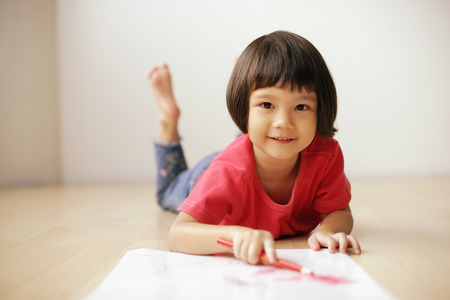 3 4 years: Young girl drawing, looking at camera